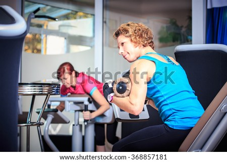 young woman on a fitness machine in a gym - stock photo