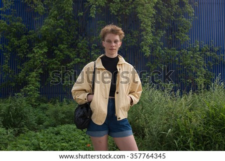 Young woman on a herbage wall