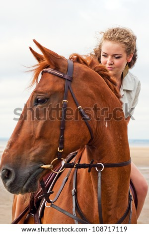 young woman on a horse - stock photo