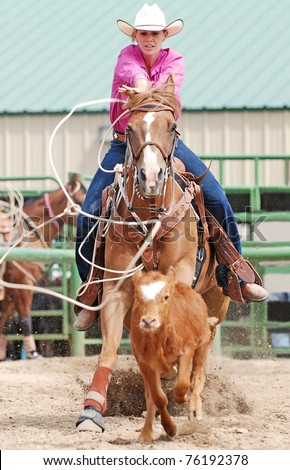 Young woman on a horse roping a calf in a rodeo competition. Motion blur with calf and rope. - stock photo