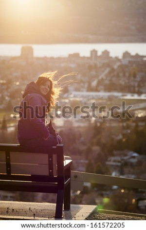 Young Woman on a Park bench at sunset - stock photo