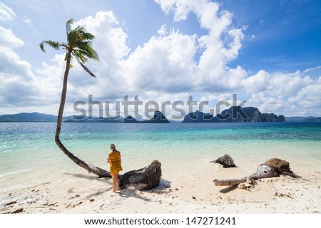 Young woman on a perfect palm beach in Philippines