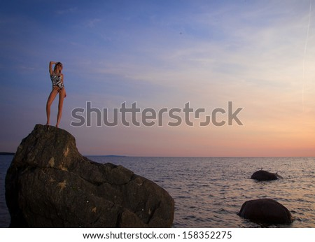 young woman on a rock by the ocean and watching the sunset