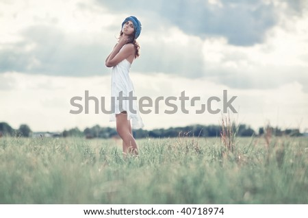 Young woman on a summer field. Soft bright colors. - stock photo