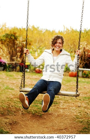 Young Woman on a Swing in the Fall - stock photo