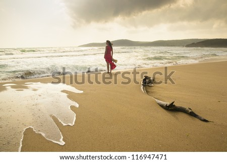 Young woman on a wild beach enjoying the natural beauty - stock photo
