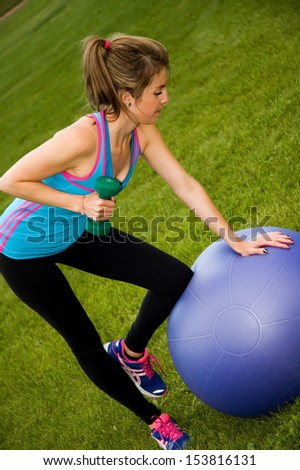 Young woman on an exercise ball, doing triceps kickbacks, in a park. - stock photo