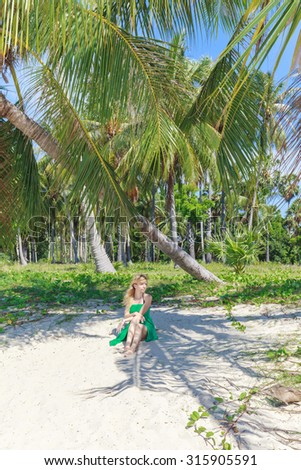 Young woman on beautiful tropical beach with palm trees, white sand and blue sky - stock photo
