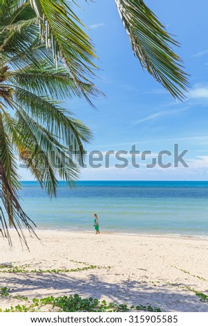 Young woman on beautiful tropical beach with palm trees, white sand, turquoise ocean water and blue sky - stock photo