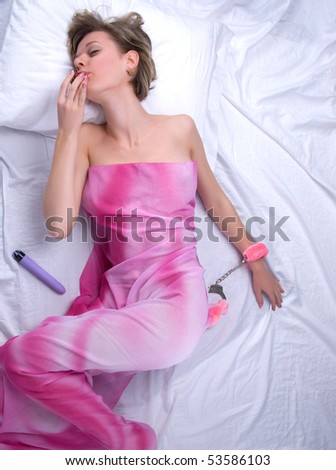 Young woman on bed with strawberry and sex toys - stock photo