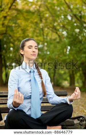 young woman on bench in park doing yoga - stock photo