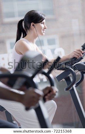 Young woman on bike at gym, exercising and listening to music - stock photo