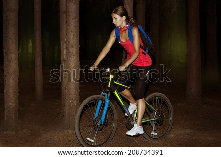 Young woman on bike outdoors - stock photo