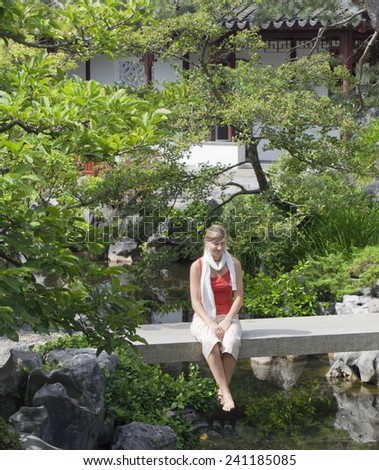 Young Woman on Bridge in Chinese Garden - Dr. Sun Yat-Sen Classical Chinese Garden, Vancouver, British Columbia, Canada - stock photo