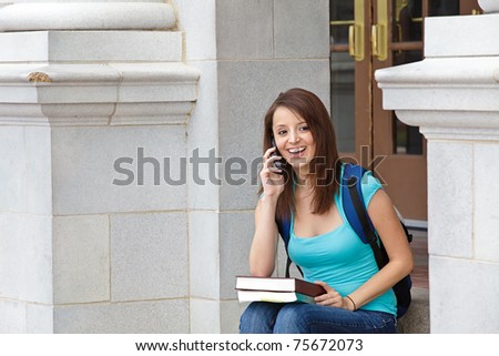 Young woman on cell phone at school - stock photo