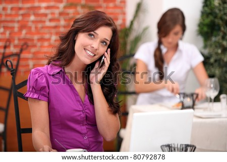 Young woman on cellphone in a restaurant