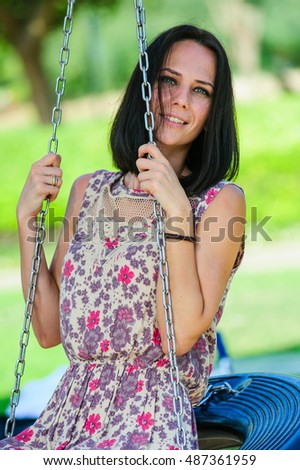 Young woman on children playground chain swings.