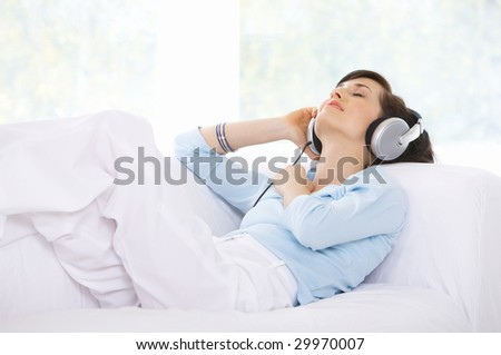 Young woman on couch and listen to the music