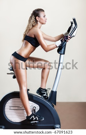 Young woman on exercise bicycle. On wall background. - stock photo