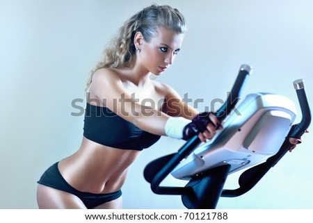 Young woman on exercise bicycle. Soft blue tint. - stock photo