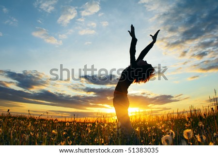 Young woman on field under sunset light - stock photo