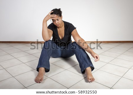 Young woman on floor, despondent. - stock photo