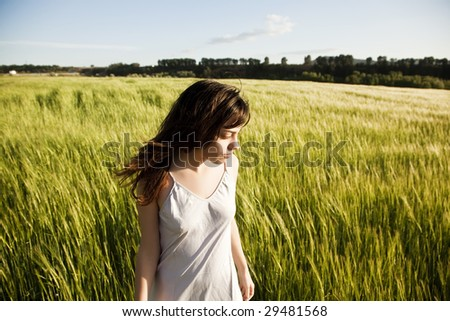 Young woman on green meadow. - stock photo