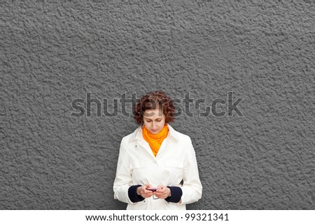 Young woman on grey wall with her smartphone - stock photo