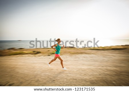 Young woman on her evening jog along the seacoast (motion blurred image) - stock photo