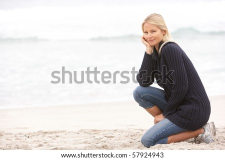 Young Woman On Holiday Kneeling On Winter Beach