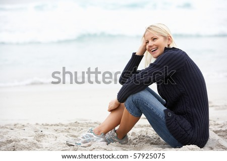 Young Woman On Holiday Sitting On Winter Beach