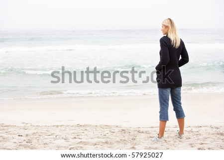 Young Woman On Holiday Standing On Winter Beach