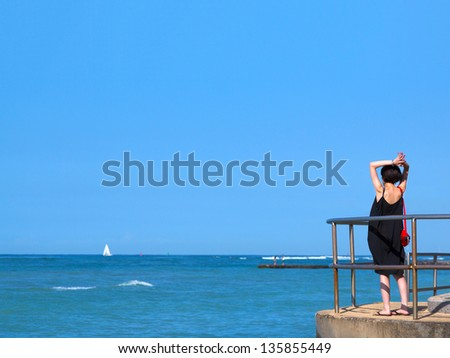 Young woman on jetty watching sea and bluesky