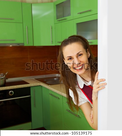 Young woman on kitchen near refrigerator - stock photo