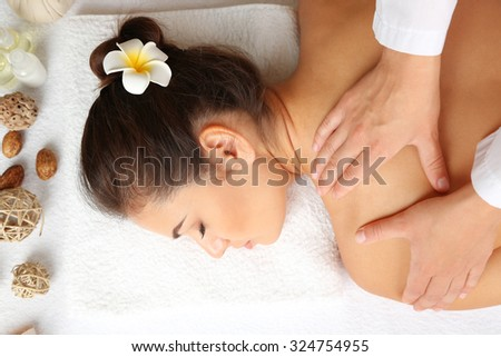 Young woman on massage table in beauty spa salon - stock photo