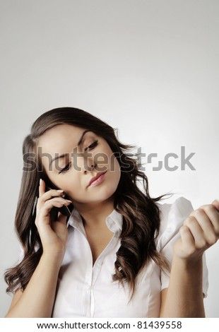 young woman on moblie telephone looking at her nails and talking - stock photo