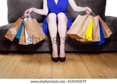 Young woman on modern gray sofa with a bunch of shopping bags