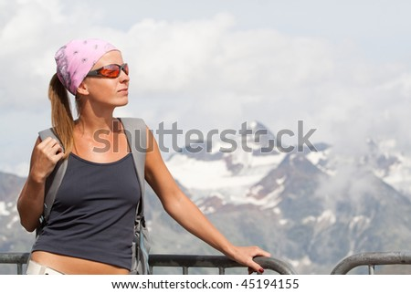Young woman on move enjoying the sun high in the mountains - stock photo