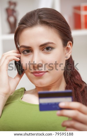 young woman on phone holding credit card at home - stock photo