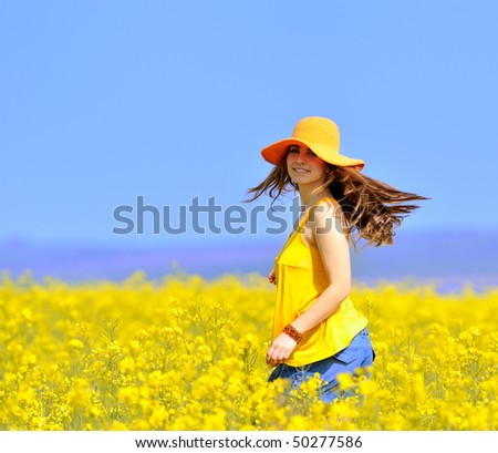 young woman on rapeseed field in bloom - stock photo