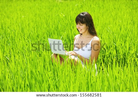 young woman on rice field with laptop computer