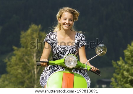 Young woman on scooter - stock photo