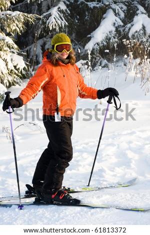 Young woman on ski in orange ski jacket - stock photo
