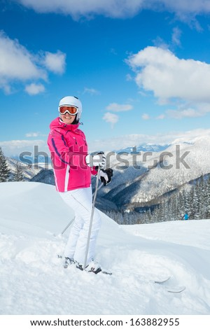 Young woman on skis in soft snow in the mountains