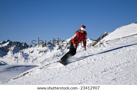 Young woman on snowboard on the slope of mountain at sunny day