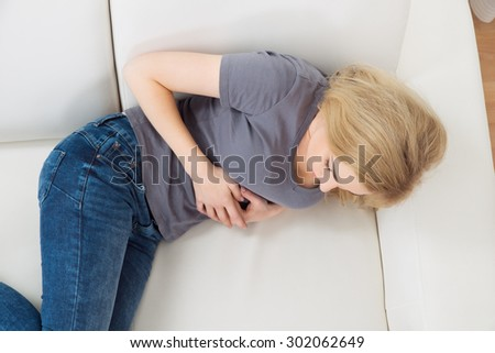 Young Woman On Sofa Suffering From Stomachache - stock photo