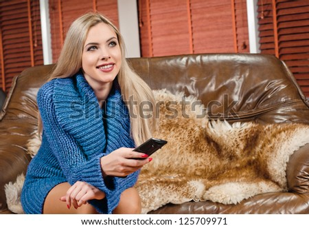 young woman on sofa with TV remote in the apartment - stock photo