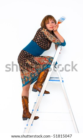 young woman on step-ladder with paint brush photo - stock photo