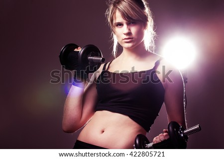 young woman on studio doing her workout welghtlifting dumbbell - stock photo