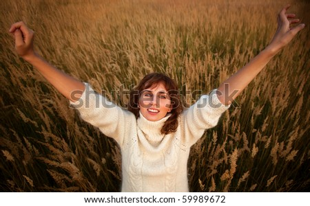 Young woman on summer field stretching up.